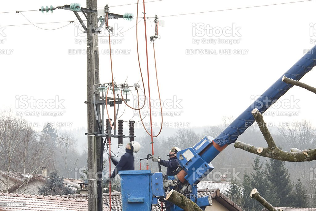 Men operate on an electric pole royalty-free stock photo
