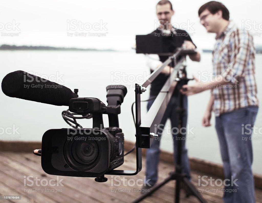 Men operating video camera on elongated tripod stock photo