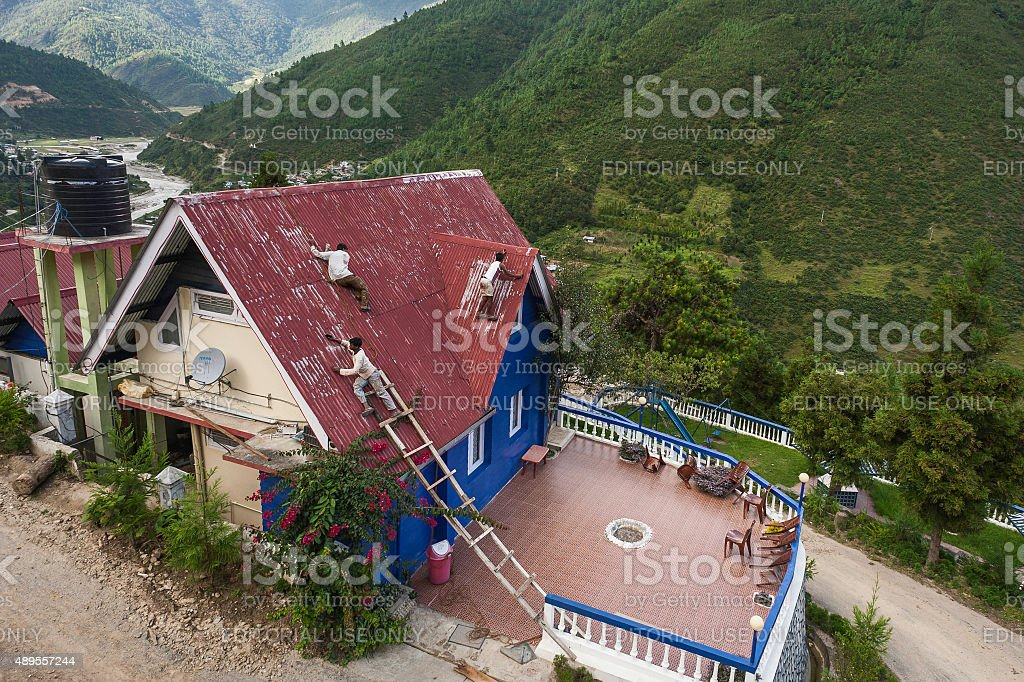 Men paint roof of house , Dirang, Arunachal Pradesh, India. stock photo