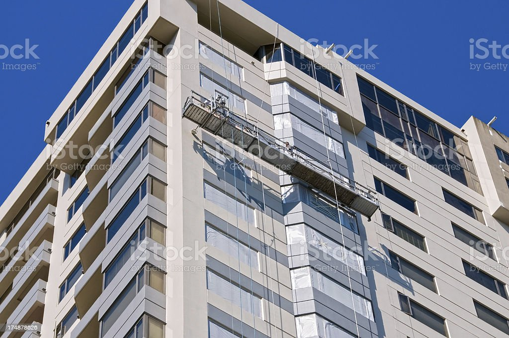 Men painting condominium's upper stories from platform royalty-free stock photo