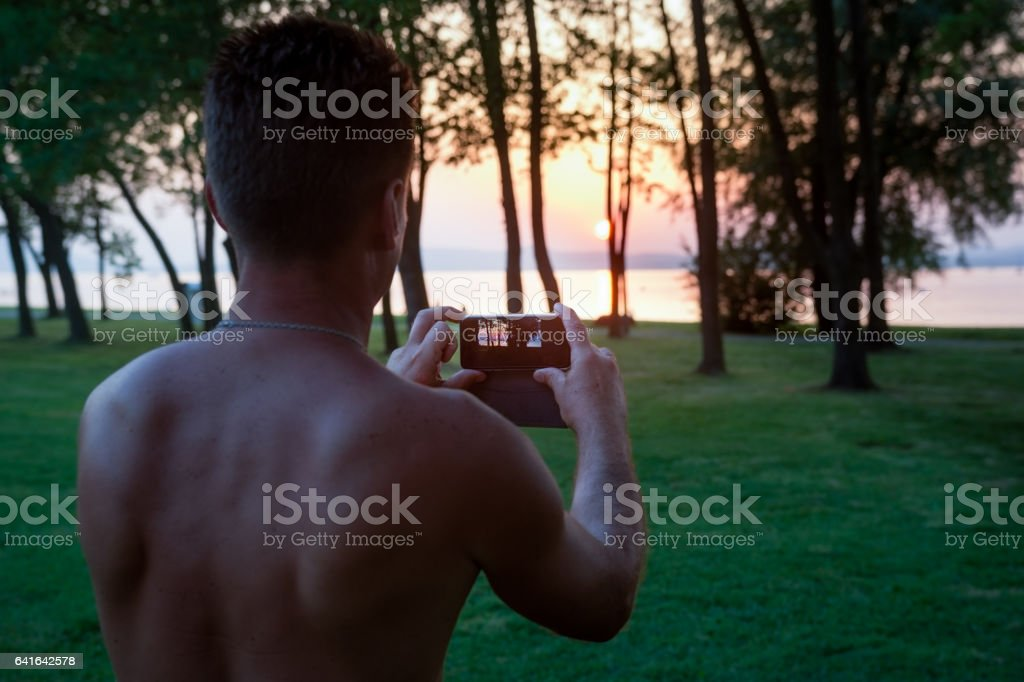 Men photographing sunset with mobile phone stock photo