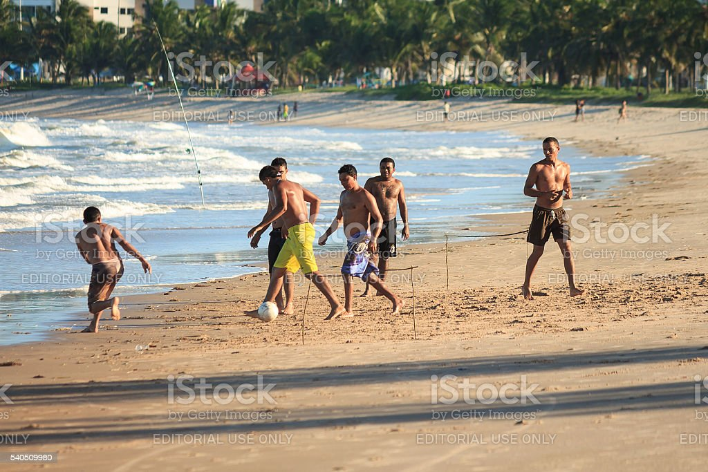 Men play football on the beach stock photo