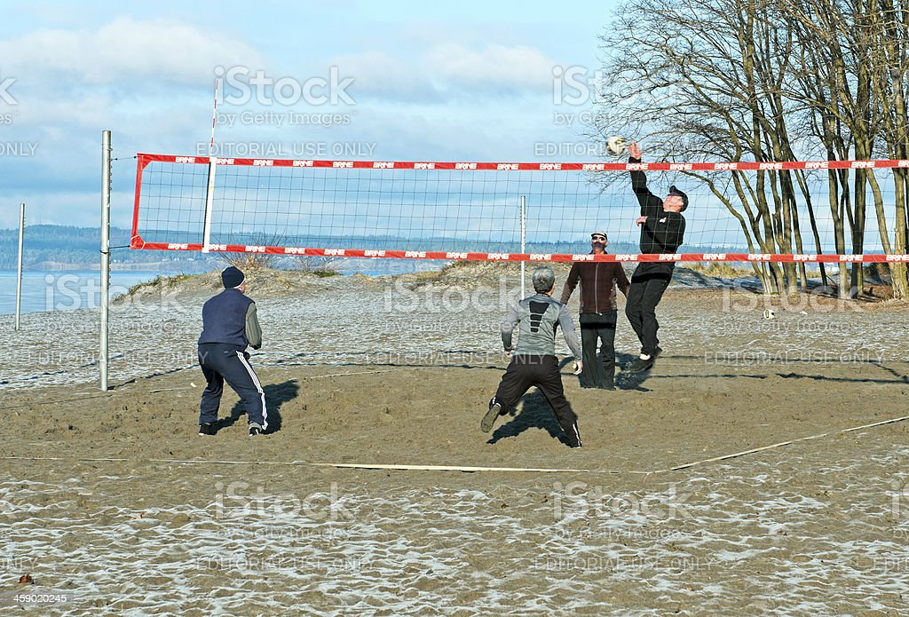 Men play volleyball at a beach in winter royalty-free stock photo