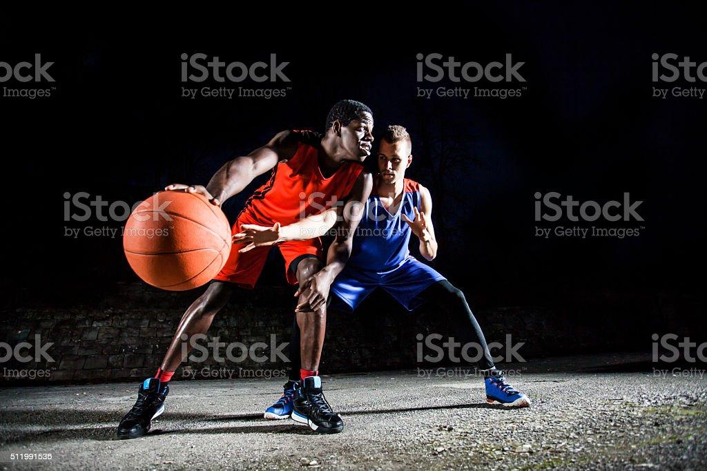 Men playing basketball at night stock photo