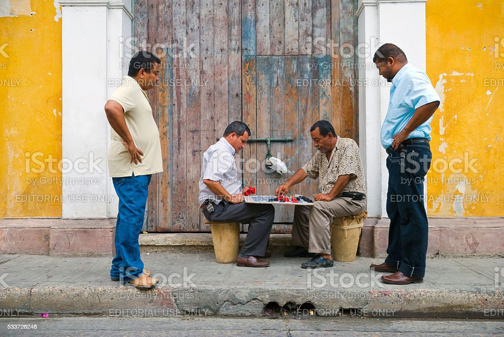 Men playing chess on sidewalk in Cartagena, Colombia stock photo