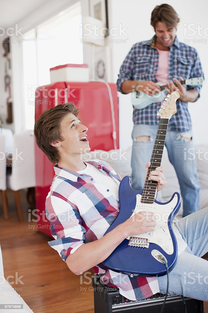 Men playing electric guitar and ukulele royalty-free stock photo