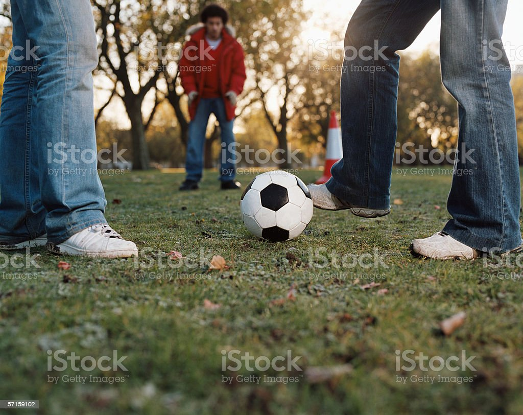 Men playing football in park royalty-free stock photo