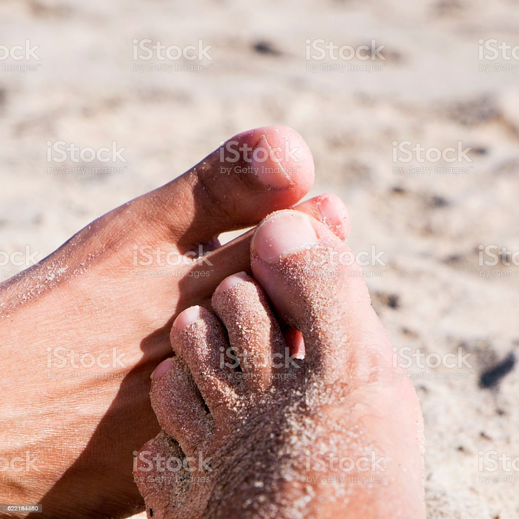 men playing footsie on the beach stock photo