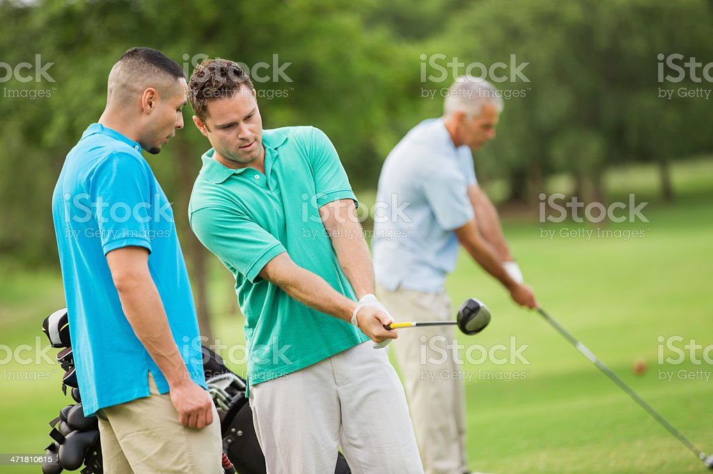 Men playing golf together on sunny day stock photo