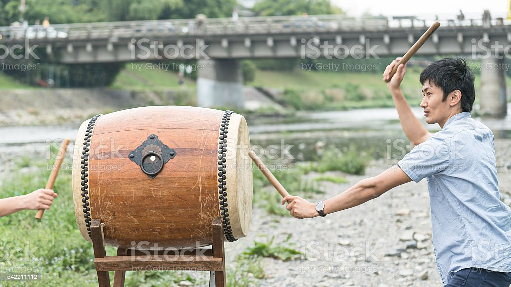 Men playing Japanese drum out of doors stock photo
