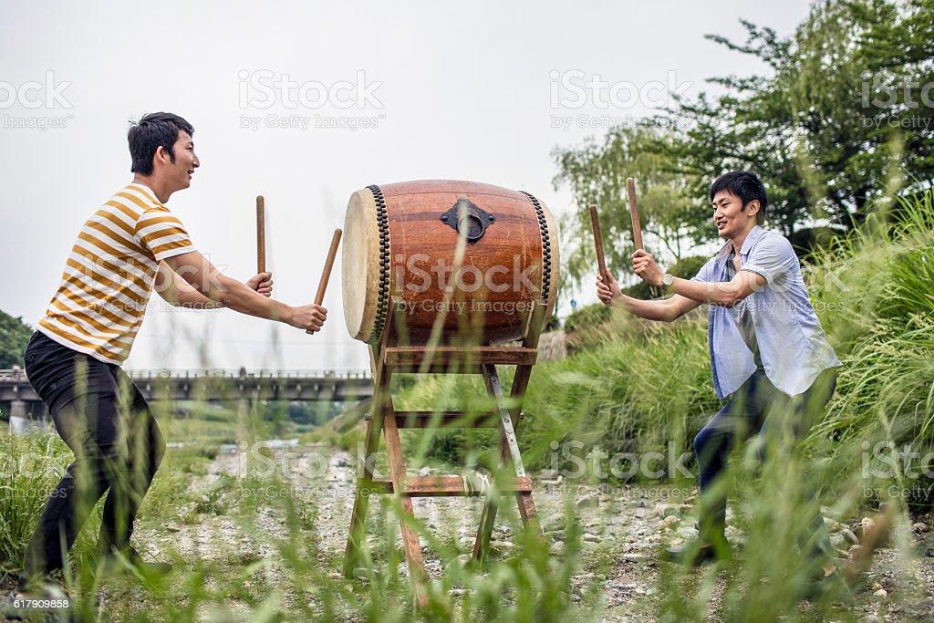 Men playing japanese taiko drum outdoors stock photo
