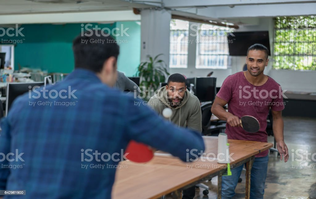Men playing ping-pong at the office stock photo