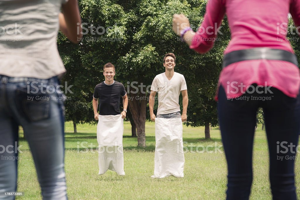 men playing sack race with girlfriends cheering stock photo