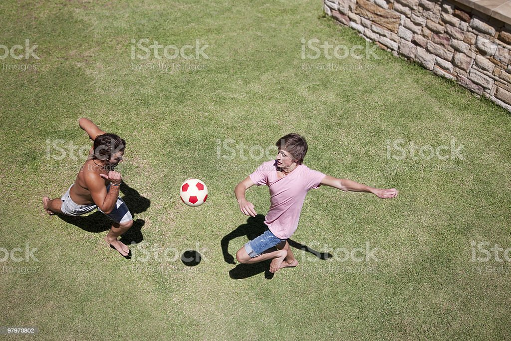 Men playing soccer on grass royalty-free stock photo