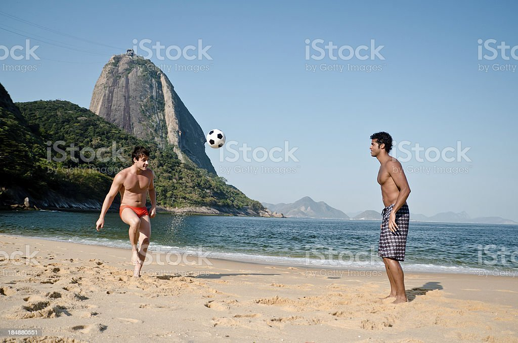 Men playing soccer on the beach royalty-free stock photo