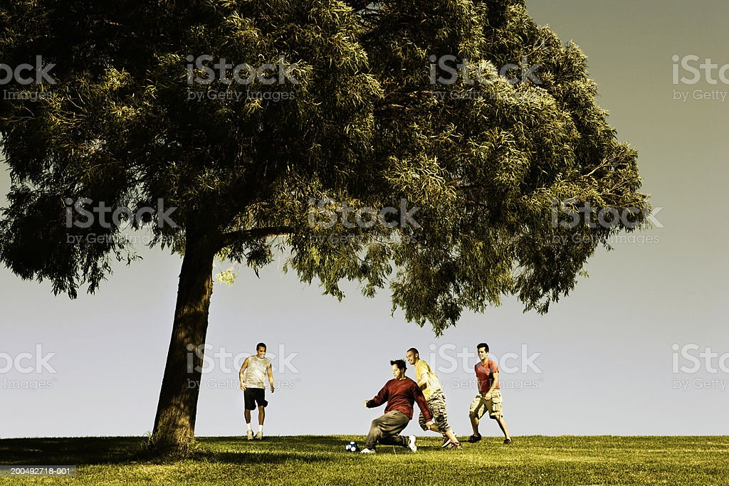 Men playing soccer under tree royalty-free stock photo