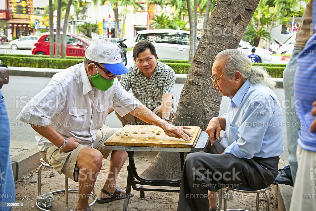 Men playing traditional board game in Saigon, Vietnam. royalty-free stock photo