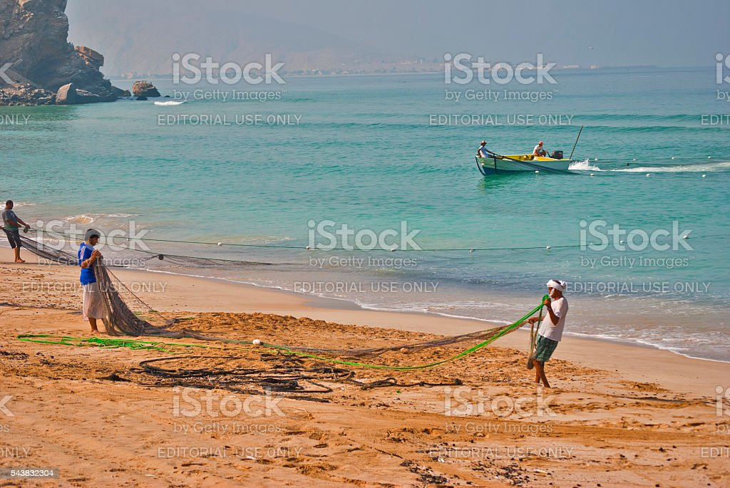 Men pulling in fishing net, Khasab, Oman stock photo