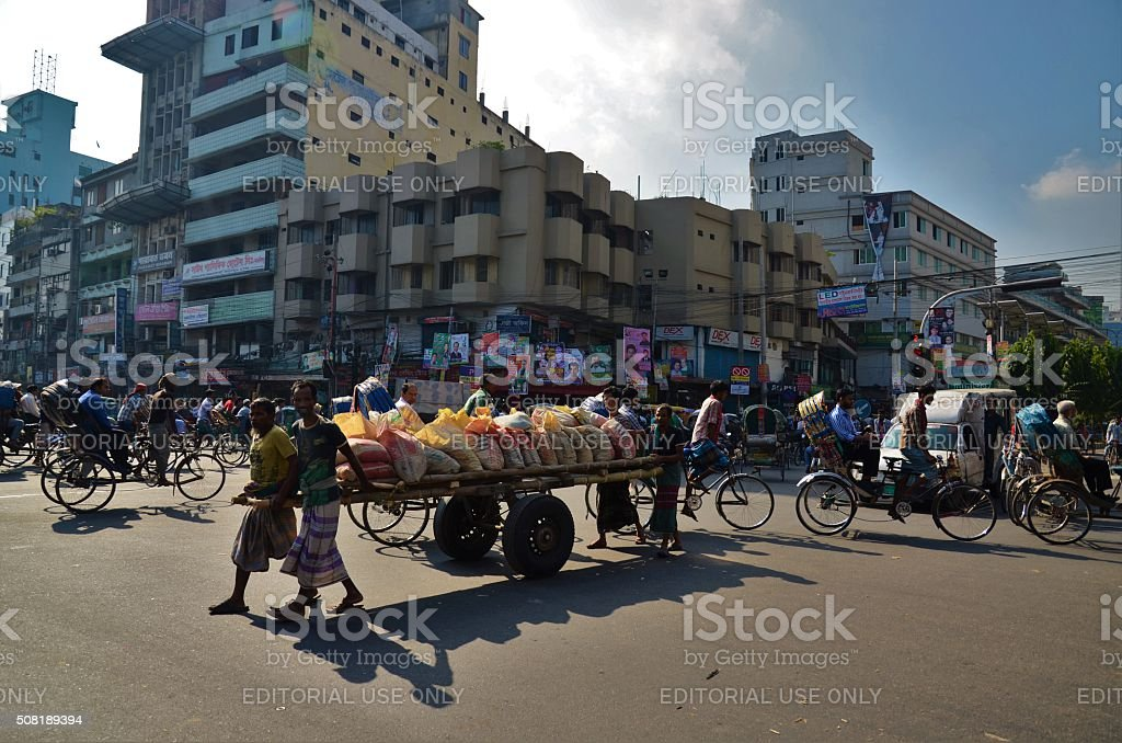 Men pushing wagon of bags in Dhaka stock photo