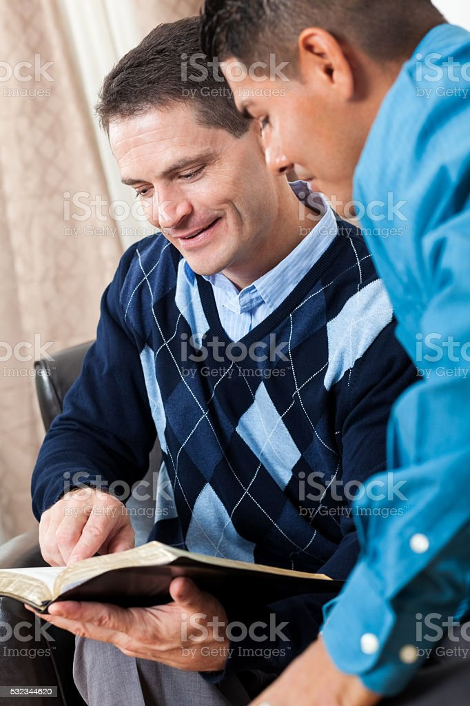 Men read the Bible together stock photo