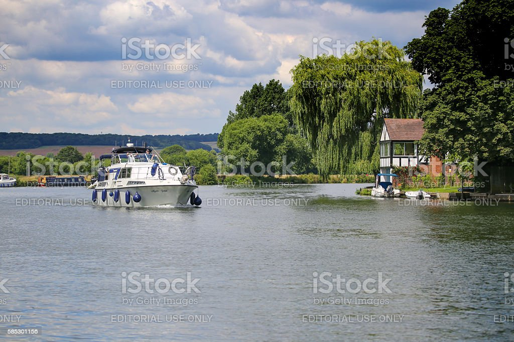 2 men relaxing on a motorboat, cruising along the Thames stock photo