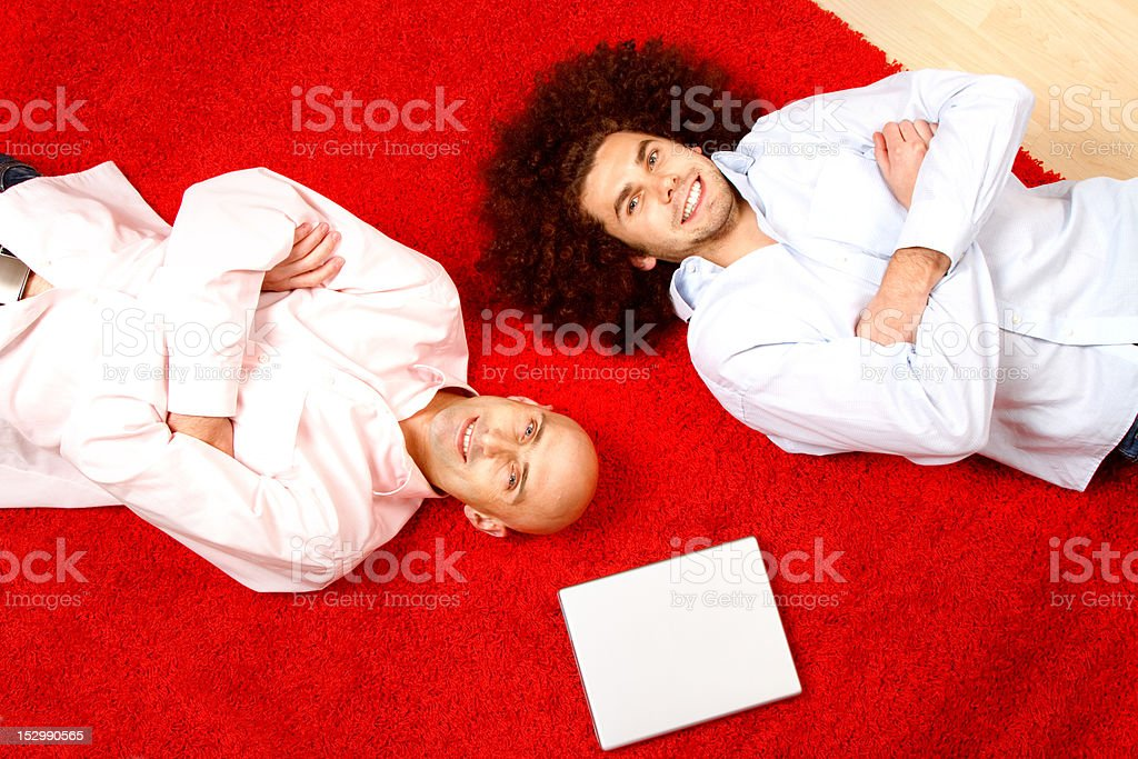 Men relaxing on rug royalty-free stock photo