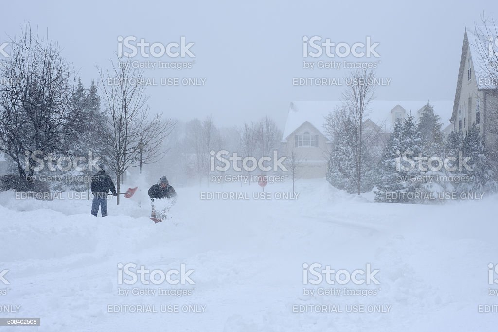 Men Removing Snow from Driveway stock photo