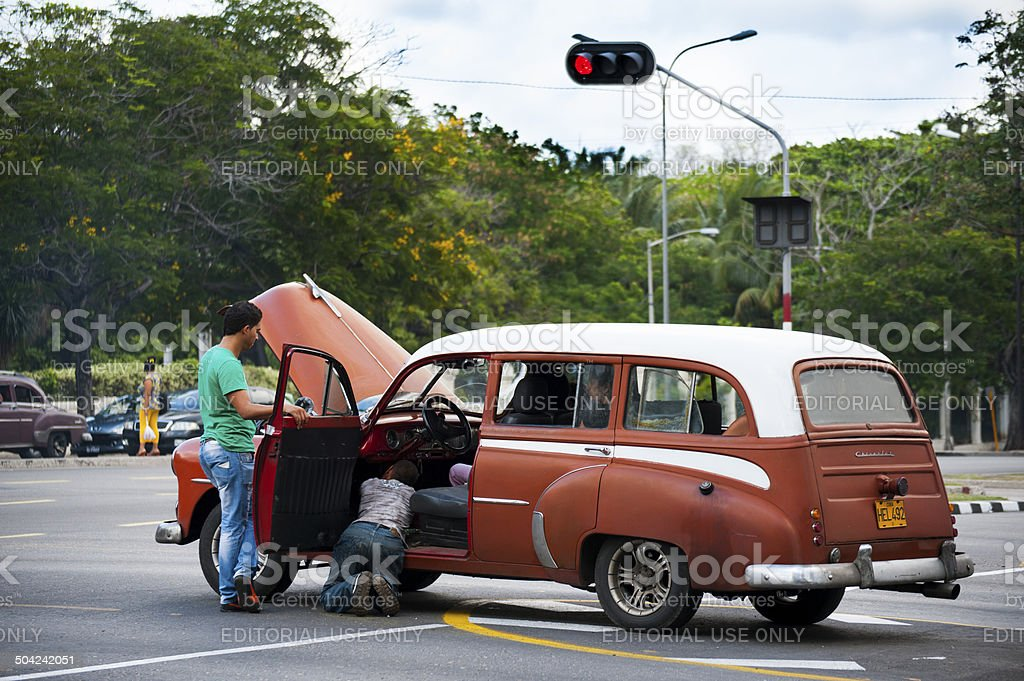 Men repair car in middle of intersection in Havana, Cuba stock photo