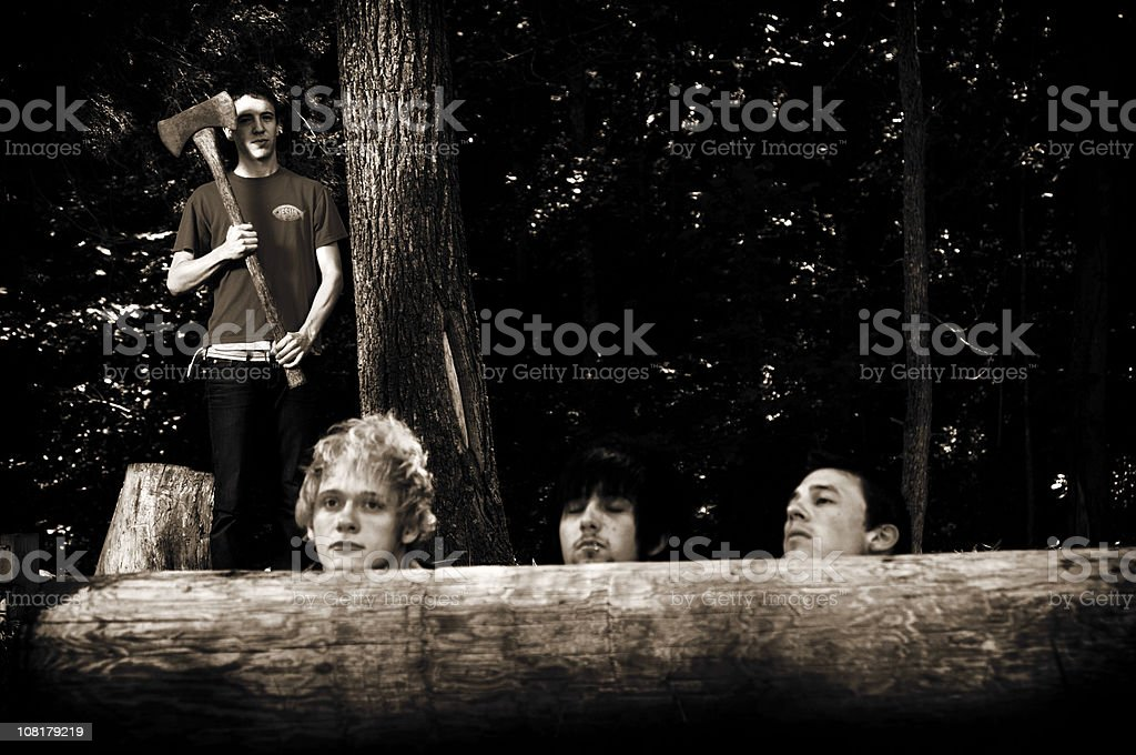 Men Resting Heads on Tree While Man Holds Axe Near stock photo