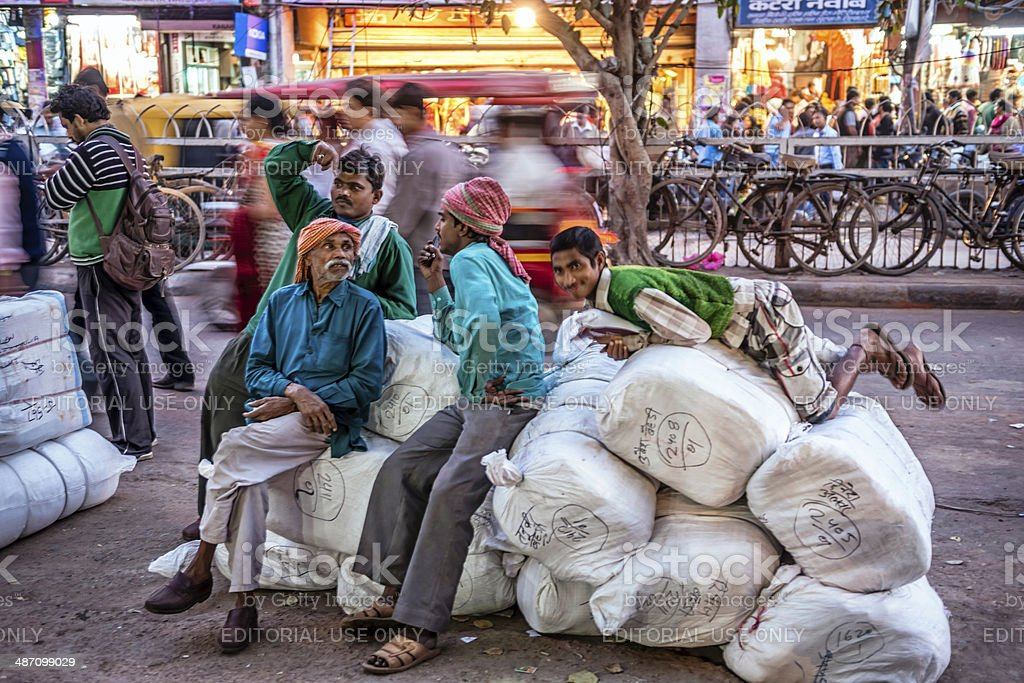 Men resting on their heavy load at Old Delhi market stock photo