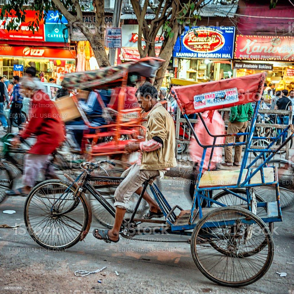 Men riding their rickshaws at Old Delhi spice market stock photo