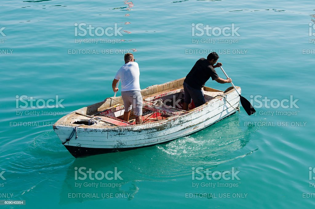 Men row in the opposite direction on the boat stock photo