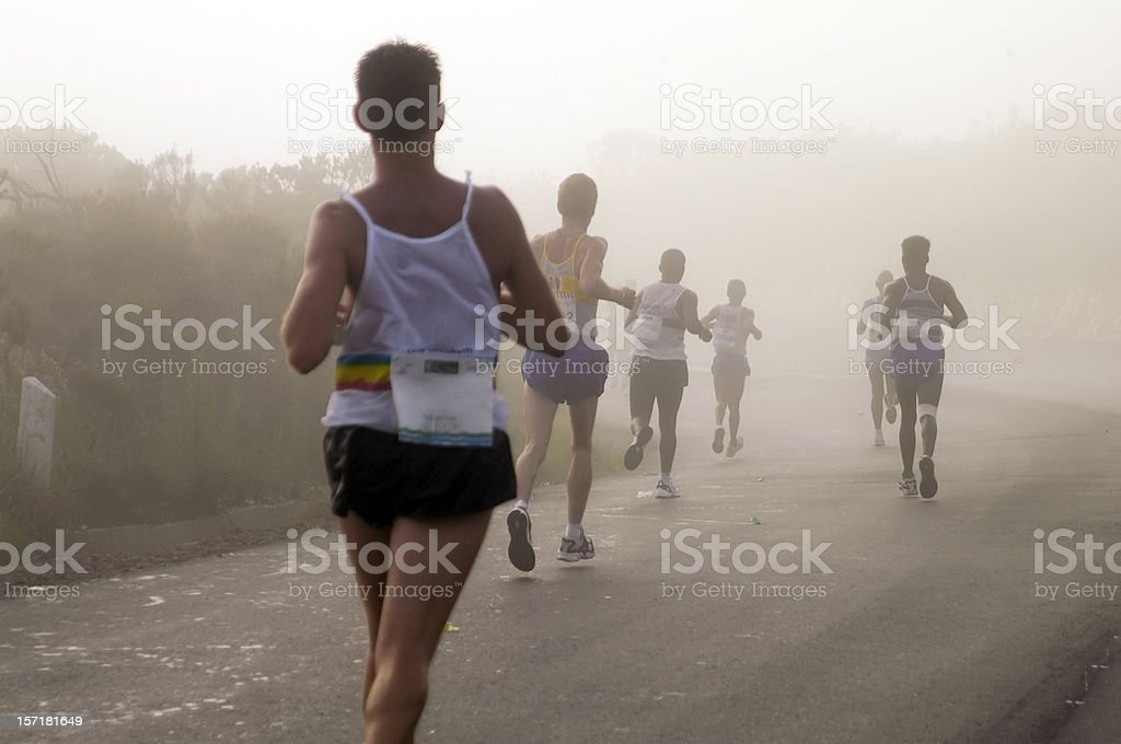 Men running in a mist while trying to win stock photo
