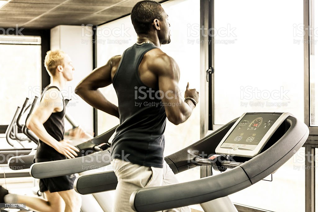 Men running on the gym treadmill stock photo