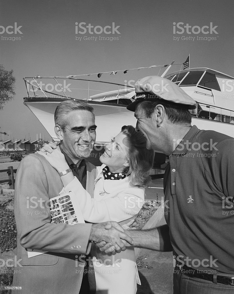 Men shaking hands while woman embracing stock photo
