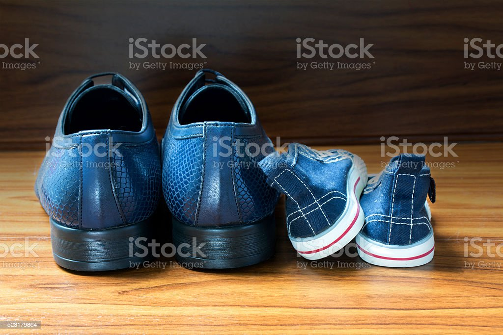 Men shoes and children sneakers side by side, father's day stock photo