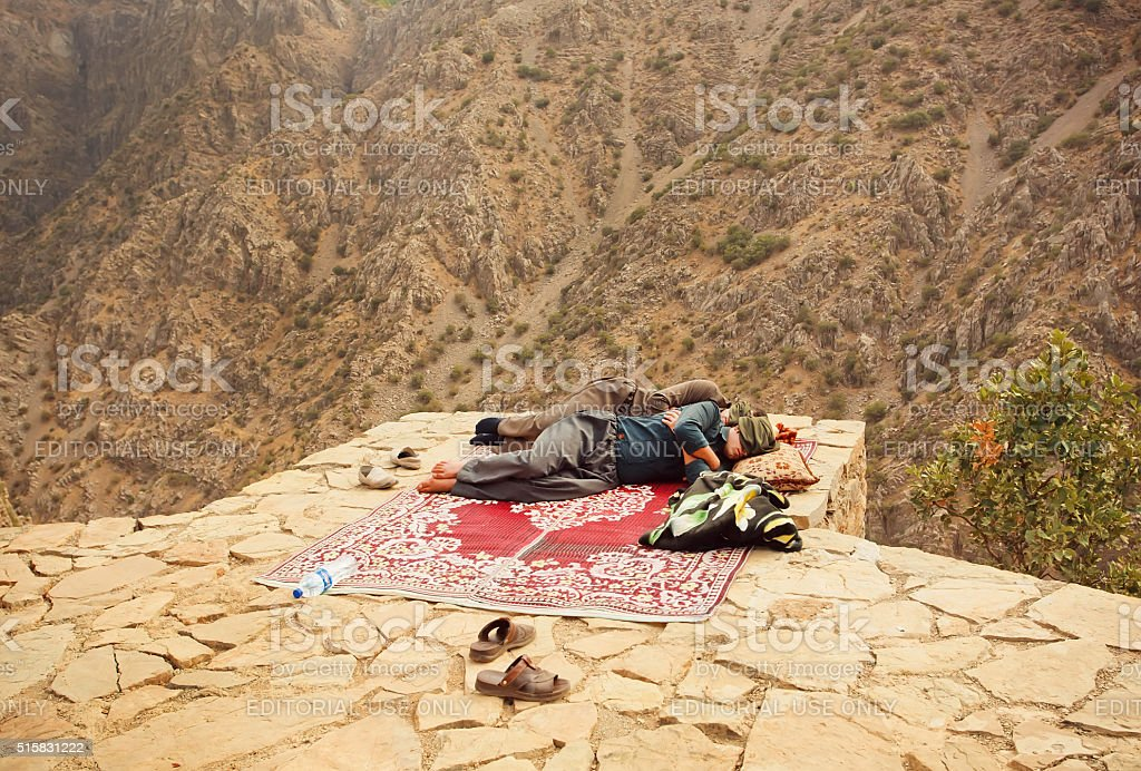 Men sleeping over a precipice in old mountaines stock photo