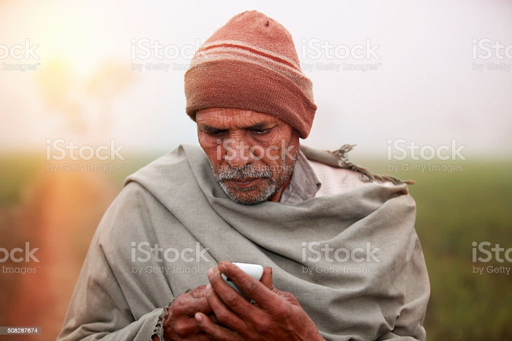 Men Standing in the Field & using mobile phone stock photo