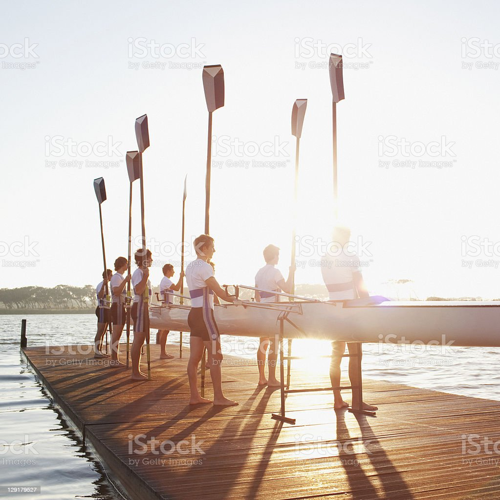 Men standing on pier with oar and canoe stock photo