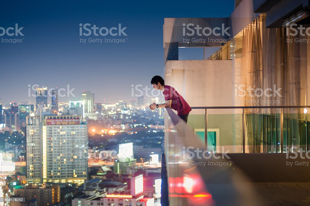 Men standing on the rooftop of a skyscraper over  cityscape stock photo