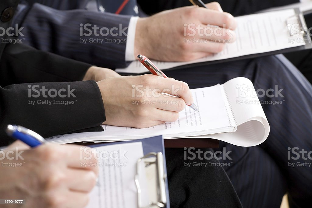 Men taking notes at a work conference with pen and paper stock photo