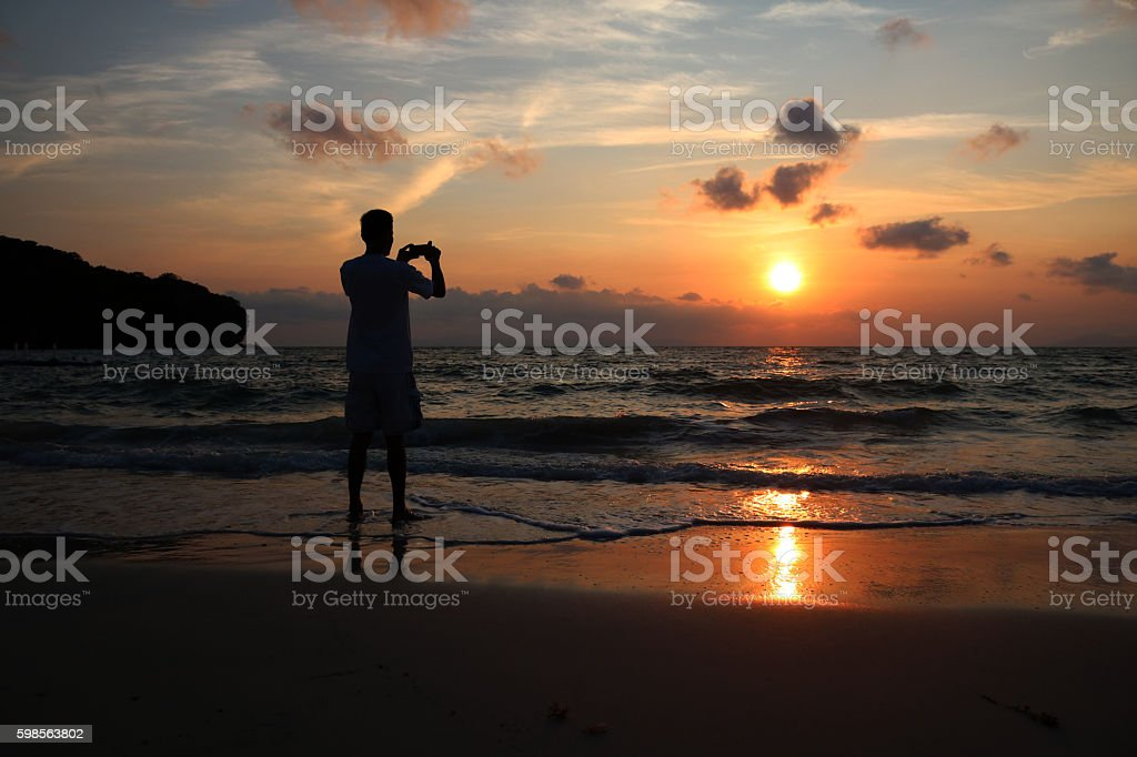 Men use phone on the beach. stock photo
