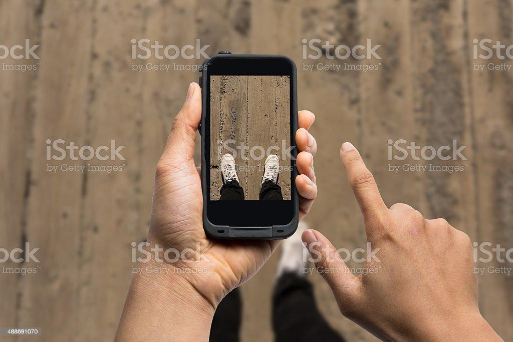 men using smart phone taking photo of his feet stock photo