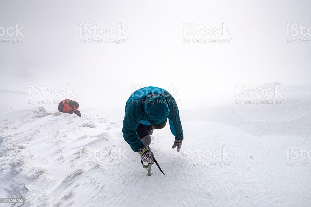 2 men walking along snowy mountain peak into the clouds stock photo