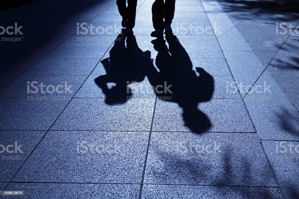 Men walking in sinister blue night shadows stock photo