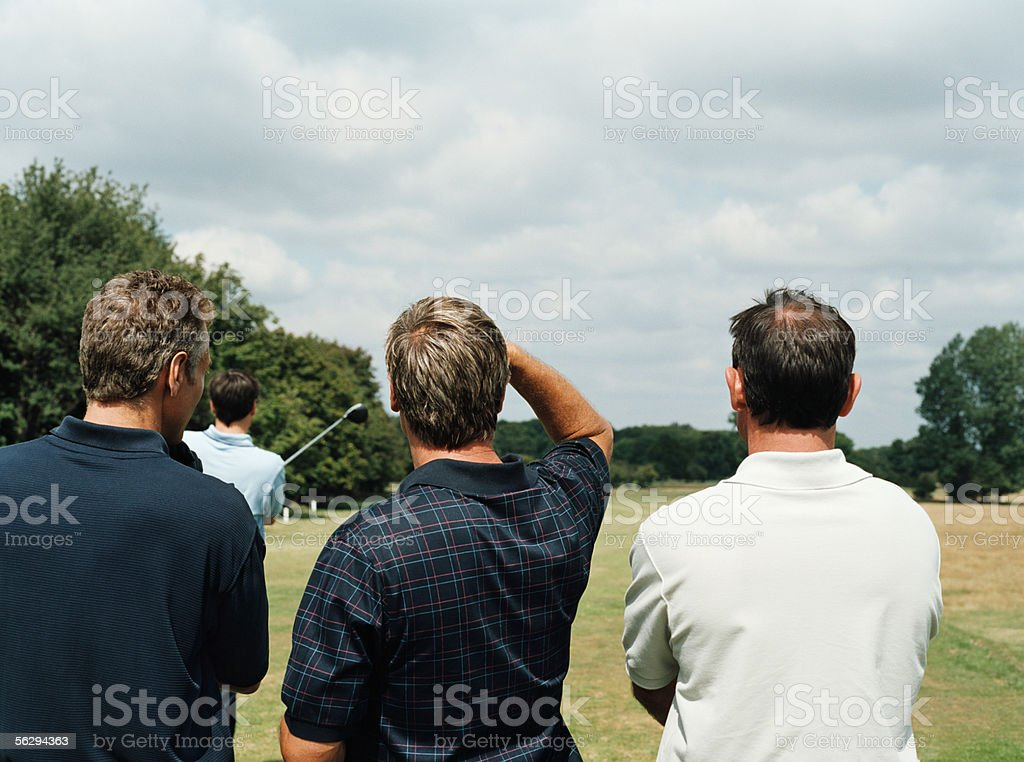 Men watching opponent playing golf royalty-free stock photo