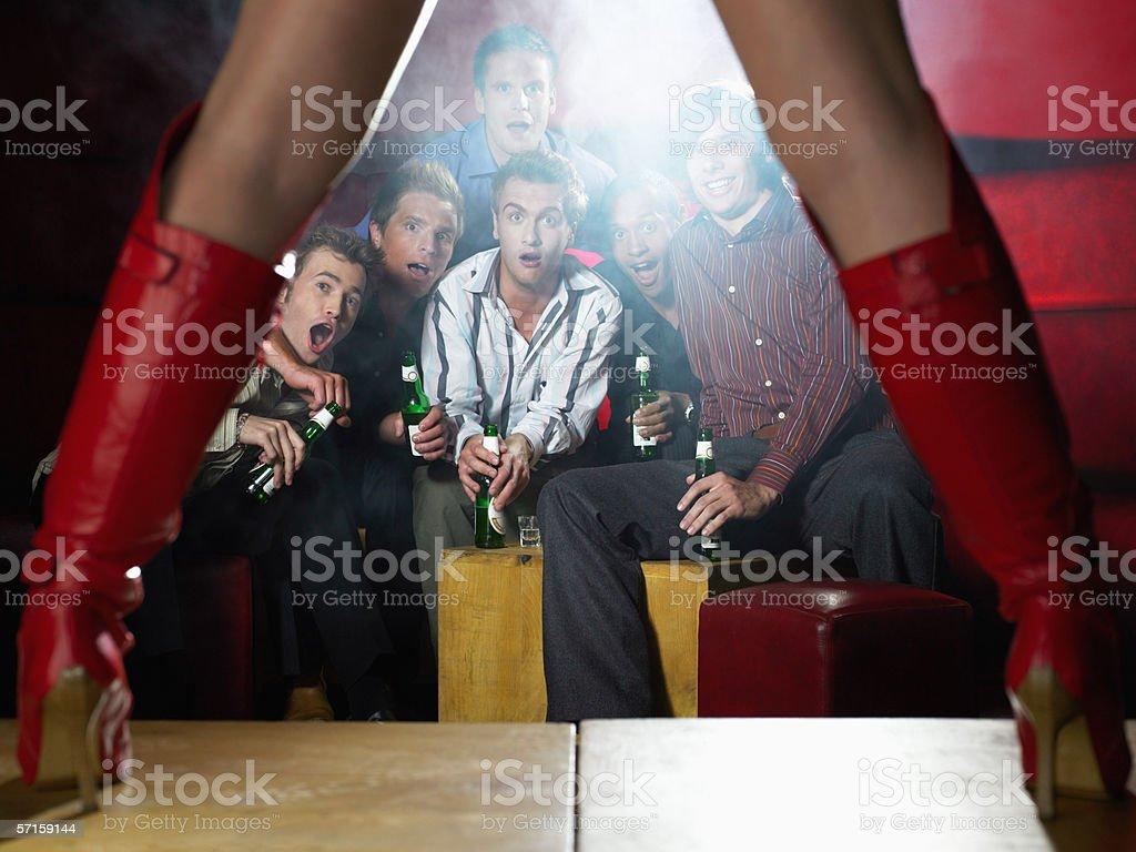 Men watching strip tease stock photo