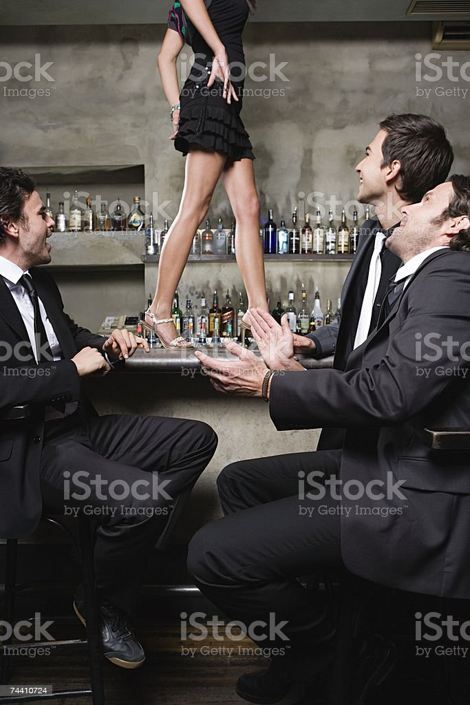 Men watching women walk on bar stock photo