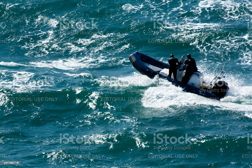 Men wearing wetsuits on a boat with an outboard motor. stock photo
