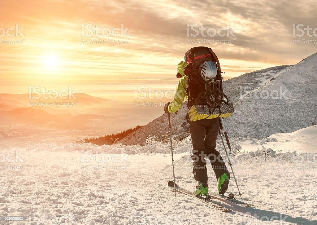 Men with backpack at ski goes to the top stock photo